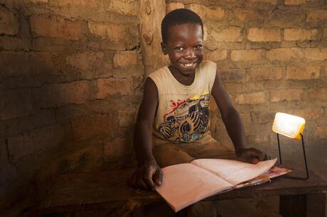 Child smiling while using a solar light to read